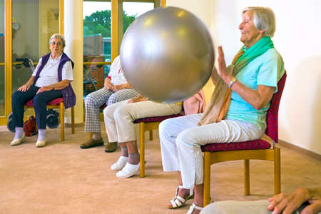 Elderly ladies working out with a pilates ball doing exercsies in a seniors gym in a wellness and healthy lifestyle concept