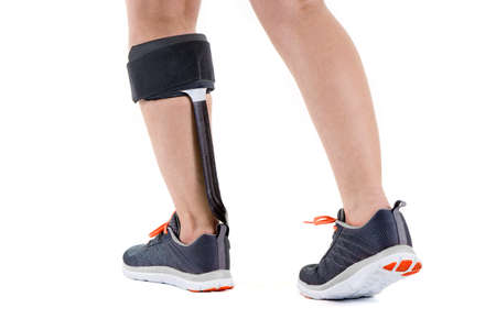 Close Up Rear View of Person in Athletic Sneakers Wearing Support Brace Around Calf Leg Muscle in Studio with White Background