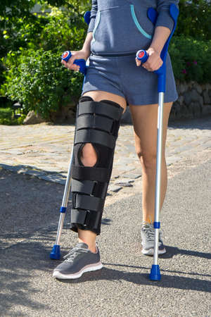 Woman wearing a leg brace with adjustable side panels to immobilize and support her knee after surgery walking on crutches outdoors on a walkway in a garden