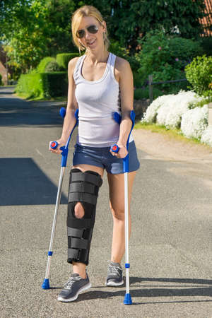 splint: Woman wearing an orthopaedic leg brace with adjustable straps to immobilise her leg following surgery or an accident walking on crutches outdoors