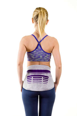 three quarter length: Three Quarter Length Rear View of Athletic Woman Wearing Modern Orthopedic Lower Back Brace for Support in Studio with White Background