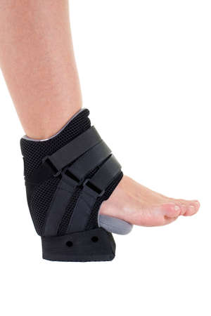 Close Up of Person with Foot and Ankle Wrapped in Modern Cast Secured with Velcro Straps in Studio with White Background with Copy Space 写真素材