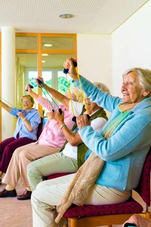 Hogere vrouwen die een training in een sportschool voor gepensioneerden zitten in hun stoelen doen rekoefeningen met elastiek om de mobiliteit en kracht in hun armen te verbeteren Stockfoto