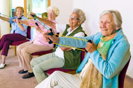 stretching: Grupo de cuatro mujeres mayores sonrientes de entonar sus brazos con bandas elásticas de refuerzo mientras se está sentado en la clase de gimnasia