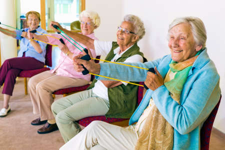 Group of four smiling senior women toning their arms with elastic strengthening bands while seated in fitness class Standard-Bild