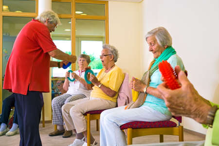 retirees: Instructor in red shirt explaining to group of retirees how to use rings with their hands in fitness class