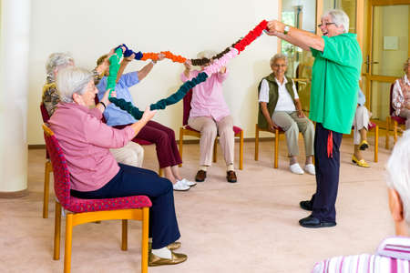 home care: Enthusiastic physical therapist holding colorful garland up with group of senior women in fitness class at retirement home