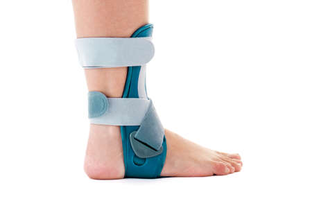 velcro: Close Up of Man Wearing Supportive Ankle Cast Brace, Secured by Velcro Straps, in Studio with White Background and Copy Space