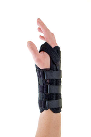 carpal tunnel syndrome: Close Up of Person Wearing Supportive Black Brace on Wrist Secured with Velcro Straps in Studio with White Background