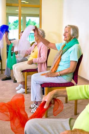 Groep vrolijke senior vrouwen zitten in stoelen zwaaien kleurrijke sjaals voor lichamelijke conditie klasse in bejaardentehuis