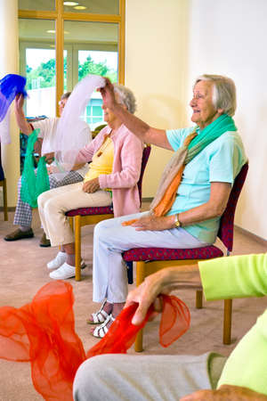 Group of cheerful senior females seated in chairs waving colorful scarves for physical fitness class at retirement home