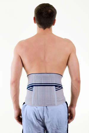 lower back pain: Rear View of Shirtless Man in Studio with White Background Wearing Orthopedic Back Brace Supporting Lower Back Pain