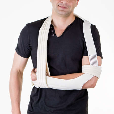 Mid Section Close Up of Man with Arm Supported in Modern Cast Sling and Standing in Studio with White Background