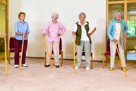 mujeres ancianas: Grupo de cuatro sonriendo mujeres pensionistas con bastones realizar ejercicios durante la clase de gimnasia en el hogar de ancianos Foto de archivo