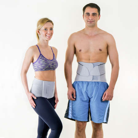 orthopedic: Portrait of Athletic Man and Woman Wearing Supportive Orthopedic Back Braces for Lower Back, Standing Together in Studio with White Background