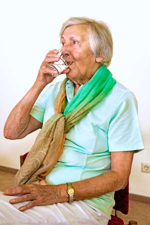 elderly woman: Serious senior woman in green scarf and shirt drinking from a glass of water while seated in chair