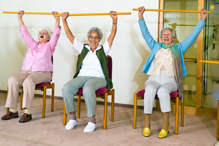 aerobic exercise: Three happy elderly ladies doing exercises in a seniors gym sitting in chairs raising wooden poles above their heads while smiling and laughing