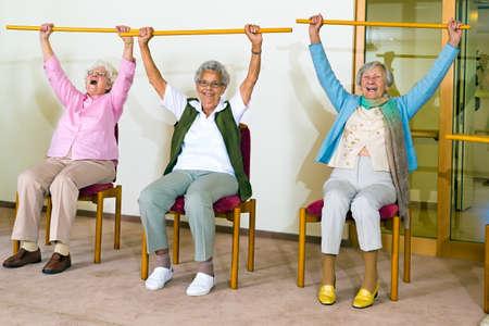 ejercicio aeróbico: Tres señoras mayores felices haciendo ejercicios en un gimnasio de la tercera edad que se sientan en las sillas de elevar postes de madera por encima de sus cabezas mientras sonriendo y riendo