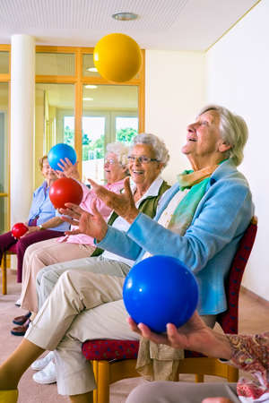coordination: Group of happy elderly ladies in a seniors gym doing hand coordination exercises throwing and catching brightly colored plastic balls as they sit in their chairs Stock Photo