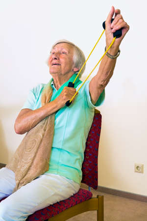 strengthen: Single elderly woman in chair using elastic stretching bands to strengthen her shoulders and arms