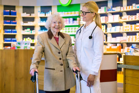 pony tail: Happy senior female patient standing with smiling doctor with pony tail and eyeglasses in front of pharmacy counter Stock Photo