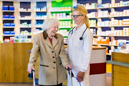 Mujer mayor de alegría en la chaqueta de color marrón con el caminante de risa con el médico femenino en vidrios tal y como están en frente del mostrador de la farmacia