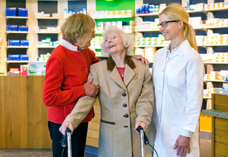 pony tail: Friendly female pharmacist in pony tail and eyeglasses talking and laughing together in front of pharmacy counter Stock Photo