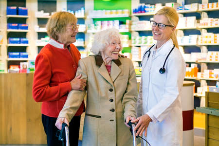 pony tail: Pair of laughing elderly women standing with friendly doctor in eyeglasses and pony tail inside a generic pharmacy