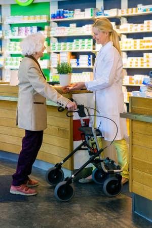 elderly woman: Helpful female pharmacist in white lab coat standing at pharmacy counter with elderly customer using wheeled walker