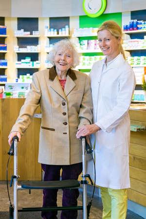 señora mayor: paciente anciano alegre en capa marrón celebración andador con la sonrisa del farmacéutico joven delante de medicamentos de venta libre