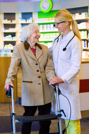 pony tail: Friendly female doctor with blond pony tail standing with elderly woman using walker in front of pharmacy counter