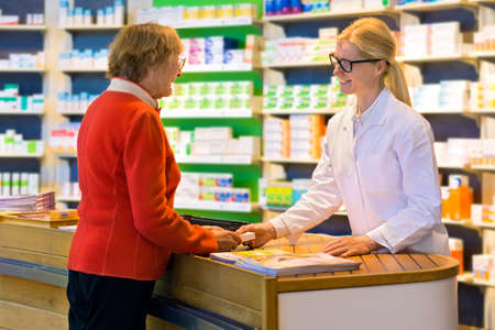 Happy senior citizen customer in red standing at pharmacy counter as pharmacist in eyeglasses and lab coat hands her a medication order Archivio Fotografico