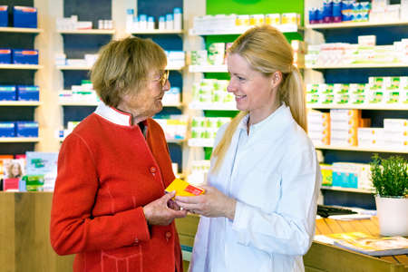 Friendly blond pharmacist in white lab coat giving happy senior woman prescription drugs while standing in front of medicine counter