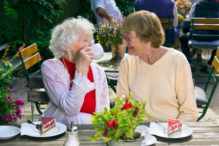 socialising: Pair of cheerful older ladies enjoying tea and cake in cafe while seated at wooden table outdoors. Stock Photo