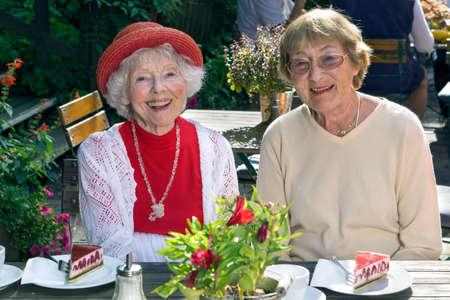 vecchiaia: Signora maggiore felice elegante in un vestito colorato estate rossa che si distende con un amico che gode di una tazza di t� e torta in un ristorante all'aperto sotto il sole.