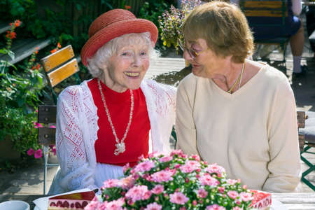 elderly people: Pair of cute senior female friends smiling and talking in front of cake and pie in outdoor cafe.