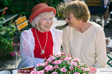 Paire de jolies amies senior souriant et parlant devant le gâteau et la tarte au café en plein air.