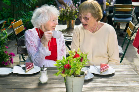 Two stylish elderly female friends relaxing over tea at an open-air cafeteria smiling and chatting as they enjoy each others company.