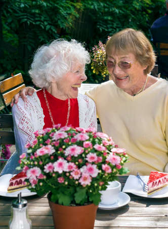 camaraderie: Two elderly ladies enjoying coffee together seated at an outdoor restaurant in summer laughing and smiling in a display of closeness and friendship. Stock Photo