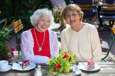 vecchiaia: Coppia di cute amichevole donne senior ridere seduto con le fette di torta sul tavolo di legno in caffè all'aperto.