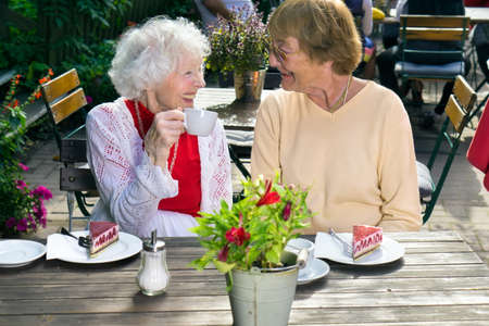 women coffee: Two senior lady friends enjoying outdoor refreshments sitting at a table on a garden patio at a restaurant smiling and chatting in the sunshine.