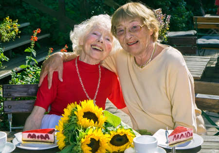 coffee and cake: Two elderly ladies enjoying their retirement having tea and cake together at an outdoor restaurant posing arm in arm smiling happily at the camera.