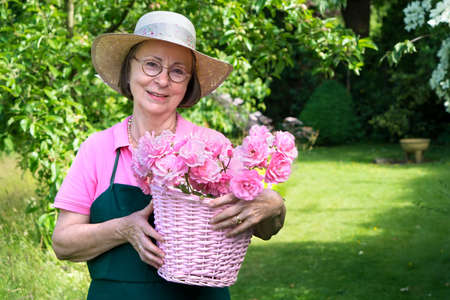 grass area: Senior female gardener in hat and apron smiling while holding basket of roses in yard during summer with copy space over grass area.