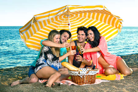 vacationing: Vacationing friends toast on the beach near a wicker picnic basket holding bread and wine while wearing swimsuits