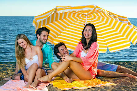 mirth: Two young smiling couples seated on sandy beach near the ocean under a large striped yellow umbrella Stock Photo