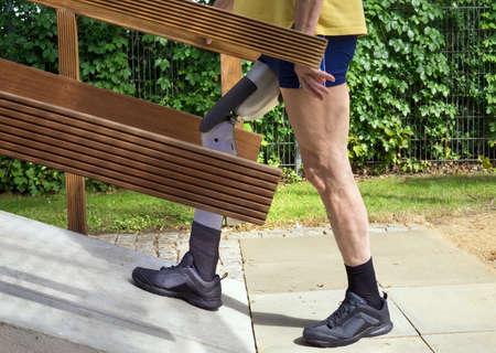 Zijaanzicht op een enkele niet-identificeerbare man in het blauw korte broek en geel overhemd lopen op betonnen oprit met beenprothese buitenshuis