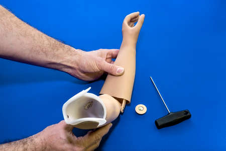 skin color: Close up on hands and tools adjusting prosthetic arm elbow joint in light skin tone color over isolated blue background