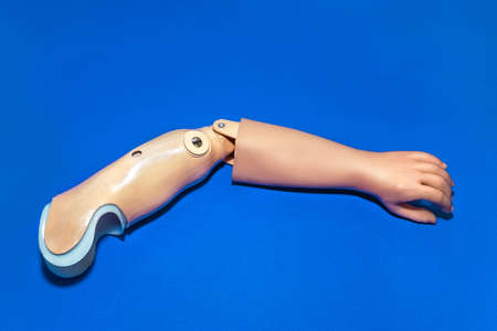 skin color: Single prosthetic arm in light skin tone color over isolated blue background