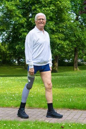 amputation: Single smiling senior man in white hair, eyeglasses and shorts walking along brick path between grass and trees with false leg Stock Photo