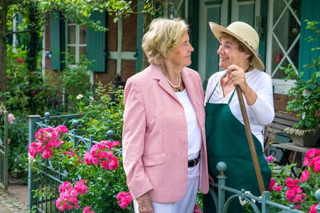 neighbours: Three Quarter Length Portrait of Two Smiling Senior Women Talking Together in Garden with Bright Pink Flowers